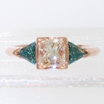 14 karat rose gold 3-stone ring with princess-cut diamond and triangular-shaped blue diamonds featured