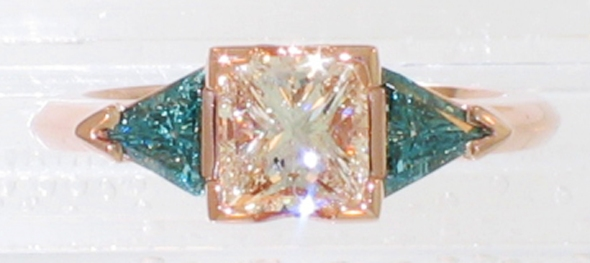 14 karat rose gold 3-stone ring with princess-cut diamond and triangular-shaped blue diamonds top down