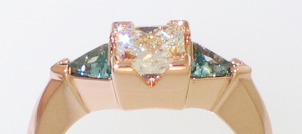 14 karat rose gold 3-stone ring with princess-cut diamond and triangular-shaped blue diamonds